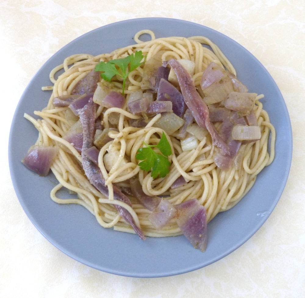 Overhead shot of plated anchovy pasta dish, with parsley garnish