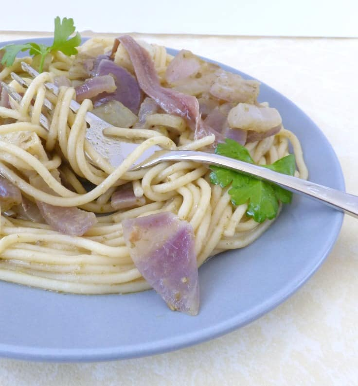 Plate of anchovy pasta with pesto, with parsley garnish and fork