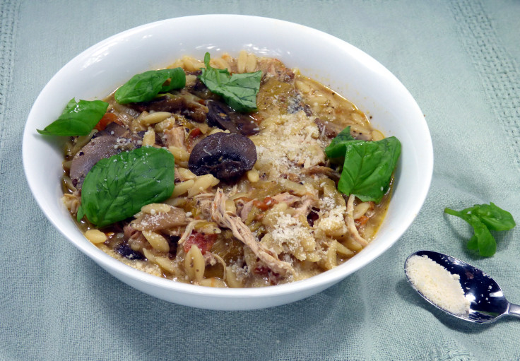 A bowl of slow cooker chicken orzo topped with parmesan and basil - an easy recipe from busylizziecooks.com