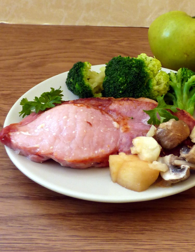 Plated bacon chop with apple, mushrooms, green vegetables, apple in background