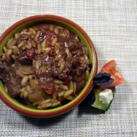 A dish of Venison Slow Cooker Giouvetsi with Greek salad on the side from busylizziecooks.com