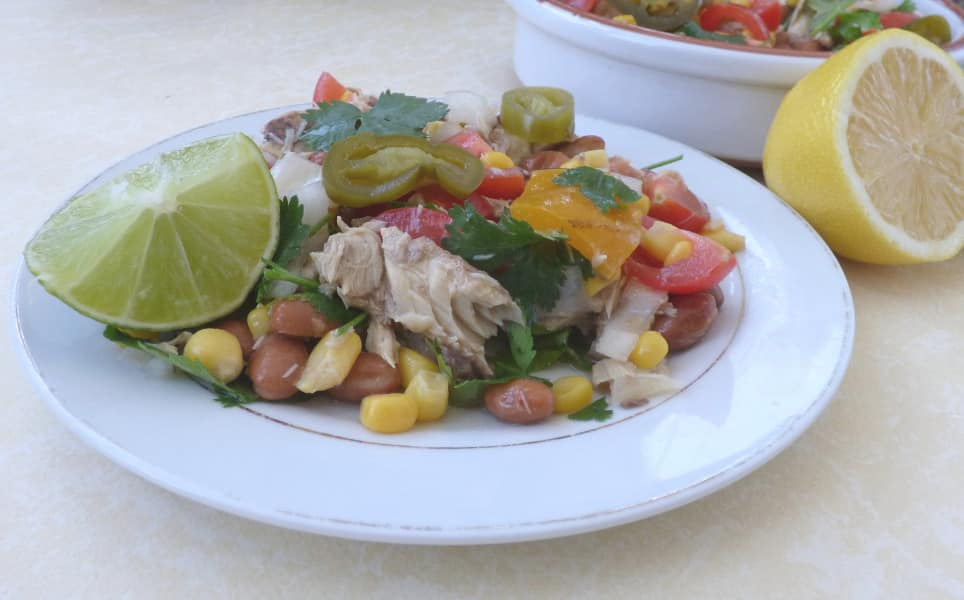 tinned mackerel salad on a plate with a lime wedge