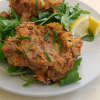 Plate of canned pilchard fish cakes with salad, garnish and lemon wedges