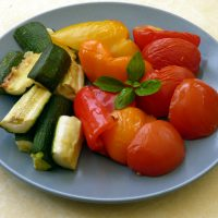 Easy Roasted Mediterranean Vegetables - courgette, tomatoes and peppers arranged on a plate with garnish